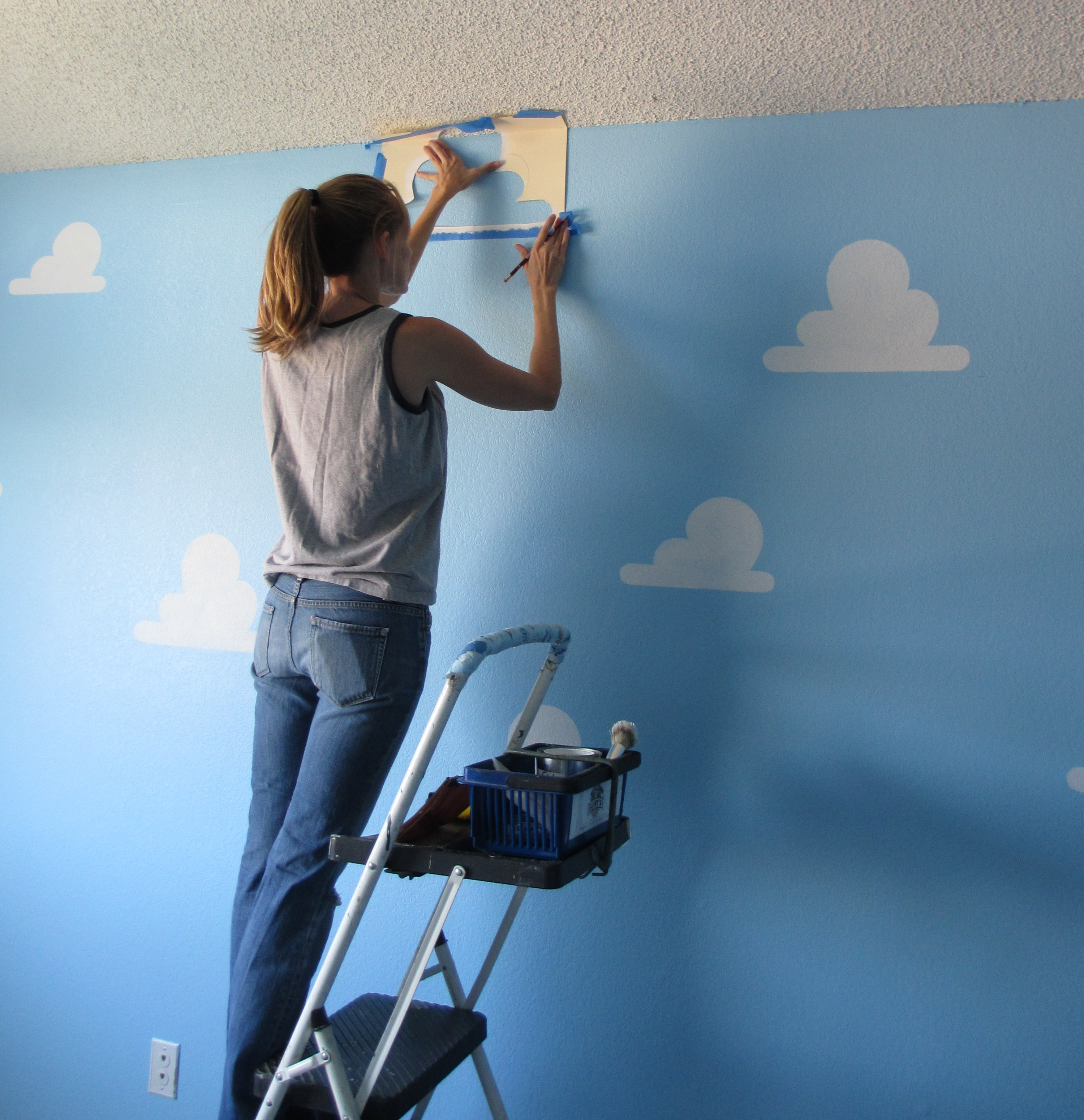 Person Painting Wall - After painting the walls blue and letting that dry you can begin the stenciling this is a two person job we followed our diagram to measure the distance